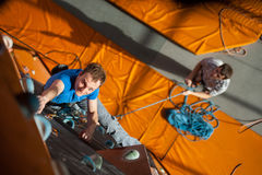 Αρσενική αναρρίχηση άσκησης βράχος-ορειβατών στον τοίχο βράχου στο εσωτερικό Στοκ Εικόνα