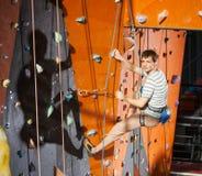 Αρσενική αναρρίχηση άσκησης βράχος-ορειβατών στον τοίχο βράχου στο εσωτερικό Στοκ Εικόνες