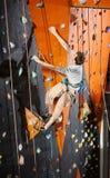 Αρσενική αναρρίχηση άσκησης βράχος-ορειβατών στον τοίχο βράχου στο εσωτερικό Στοκ Φωτογραφία