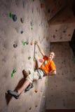 Αρσενική αναρρίχηση άσκησης ορειβατών σε έναν τοίχο βράχου στο εσωτερικό Στοκ εικόνες με δικαίωμα ελεύθερης χρήσης