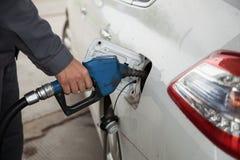 Αρσενική αντλώντας βενζίνη χεριών στο αυτοκίνητο στο βενζινάδικο στοκ φωτογραφία