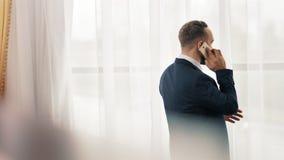 Αρσενική απάντηση επιχειρηματιών για την εισερχόμενη κλήση που χρησιμοποιεί την οθόνη επαφής του smartphone που στέκεται στο μπρο φιλμ μικρού μήκους