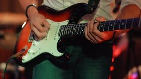 Αρσενική βαθιά κιθάρα παιχνιδιών μουσικών σε μια συναυλία βράχου απόθεμα βίντεο