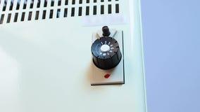 Αρσενική δύναμη ρύθμισης χεριών σε μια άσπρη ηλεκτρική θερμάστρα, ενέργεια για να θερμάνει τη μετατροπή φιλμ μικρού μήκους