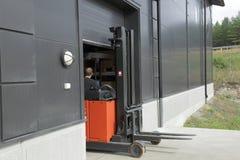 Αρσενική εκδίωξη εργαζομένων μιας αποθήκης εμπορευμάτων στο forklift-φορτηγό Στοκ Εικόνα