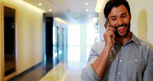 Αρσενική εκτελεστική ομιλία στο κινητό τηλέφωνο στο διάδρομο απόθεμα βίντεο