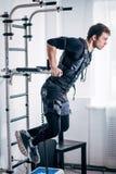 Αρσενική επίλυση EMS, που κάνει την ώθηση UPS άτομο που κάνει triceps τις εμβυθίσεις στους παράλληλους φραγμούς Στοκ εικόνα με δικαίωμα ελεύθερης χρήσης