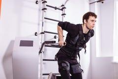 Αρσενική επίλυση EMS, που κάνει την ώθηση UPS άτομο που κάνει triceps τις εμβυθίσεις στους παράλληλους φραγμούς Στοκ Φωτογραφία
