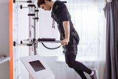 Αρσενική επίλυση EMS, που κάνει την ώθηση UPS άτομο που κάνει triceps τις εμβυθίσεις στους παράλληλους φραγμούς Στοκ Εικόνες