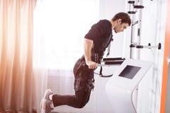 Αρσενική επίλυση EMS, που κάνει την ώθηση UPS άτομο που κάνει triceps τις εμβυθίσεις στους παράλληλους φραγμούς Στοκ Εικόνα