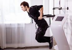 Αρσενική επίλυση EMS, που κάνει την ώθηση UPS άτομο που κάνει triceps τις εμβυθίσεις στους παράλληλους φραγμούς Στοκ Φωτογραφίες