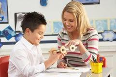 Αρσενική εργασία μαθητών και δασκάλων σχολείου πρωτοβάθμιας εκπαίδευσης στοκ φωτογραφία