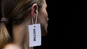 Αρσενική ετικέτα θυμάτων χεριών κρεμώντας στο γυναικείο αυτί, ταπεινωτική προσωπικότητα της γυναίκας απόθεμα βίντεο