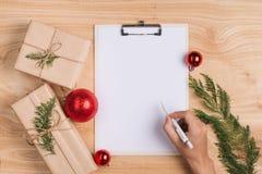 Αρσενική ευχετήρια κάρτα Χριστουγέννων γραψίματος και τυλίγοντας δώρα Χριστουγέννων  Στοκ Φωτογραφία
