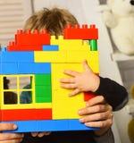 Αρσενική ζωηρόχρωμη κατασκευή χεριών και τούβλων παιχνιδιών λαβής παιδιών Στοκ εικόνα με δικαίωμα ελεύθερης χρήσης