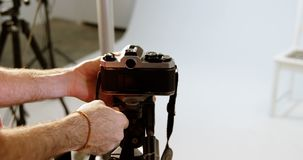 Αρσενική κάμερα ρύθμισης φωτογράφων στο στούντιο φωτογραφιών 4k απόθεμα βίντεο