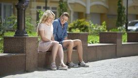 Αρσενική και θηλυκή συνεδρίαση στον πάγκο το ένα δίπλα στο άλλο, αδέξια, πρώτη ημερομηνία συναισθήματος απόθεμα βίντεο