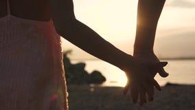 Αρσενική και θηλυκή κινηματογράφηση σε πρώτο πλάνο χεριών ενάντια στον ήλιο ρύθμισης Εξευγενίστε την αφή δύο εραστών Αγάπη, ειδύλ απόθεμα βίντεο