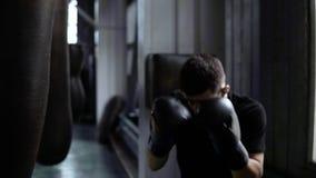 αρσενική κατάρτιση μπόξερ Κάνοντας τα ισχυρά, σκληρά χτυπήματα στον εγκιβωτισμό της τσάντας Καυκάσιος νέος τύπος workout στη γυμν φιλμ μικρού μήκους