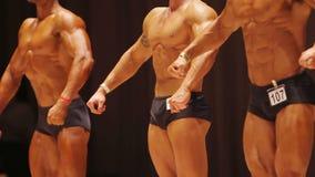 Αρσενική καυχησιολογία bodybuilders των μυϊκών οργανισμών στη σκηνή, αποτέλεσμα των σκληρών workouts απόθεμα βίντεο