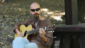 Αρσενική κιθάρα παιχνιδιού μουσικών υπαίθρια απόθεμα βίντεο