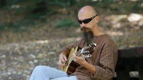 Αρσενική κιθάρα παιχνιδιού μουσικών υπαίθρια φιλμ μικρού μήκους