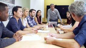Αρσενική κύρια εξετάζοντας συνεδρίαση γύρω από τον πίνακα αιθουσών συνεδριάσεων απόθεμα βίντεο