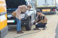 Αρσενική μηχανική αντικαθιστώντας ρόδα αυτοκινήτων πελατών εικόνων Στοκ φωτογραφία με δικαίωμα ελεύθερης χρήσης
