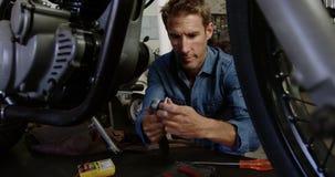 Αρσενική μηχανική μοτοσικλέτα επισκευής στο γκαράζ 4k επισκευής απόθεμα βίντεο