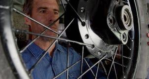 Αρσενική μηχανική ρόδα μοτοσικλετών εξέτασης στο γκαράζ 4k επισκευής φιλμ μικρού μήκους