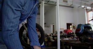 Αρσενική μηχανική ωθώντας ρόδα μοτοσικλετών στο γκαράζ 4k επισκευής απόθεμα βίντεο