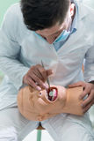 Αρσενική οδοντική άσκηση σπουδαστών στην κούκλα Στοκ Εικόνα