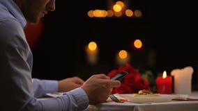 Αρσενική περιμένοντας κυρία για την ημερομηνία να τυλίξει εστιατορίων στο smartphone, χρόνος μόνο απόθεμα βίντεο