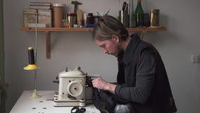 Αρσενική ράβοντας γούνα ραφτών furrier στη μηχανή στο εργαστήριο απόθεμα βίντεο