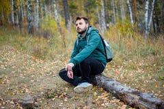 Αρσενική συνεδρίαση οδοιπόρων σε ένα πεσμένο δέντρο και στήριξη στοκ φωτογραφία με δικαίωμα ελεύθερης χρήσης