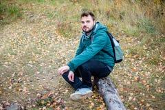 Αρσενική συνεδρίαση οδοιπόρων σε ένα πεσμένο δέντρο και στήριξη στοκ εικόνες