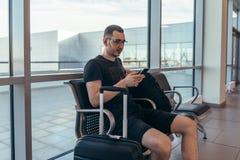 Αρσενική συνεδρίαση τουριστών στον πάγκο με τις αποσκευές στη αίθουσα αναμονής στον αερολιμένα στοκ εικόνα με δικαίωμα ελεύθερης χρήσης