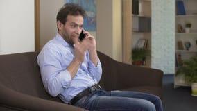 Αρσενική συνεδρίαση freelancer στον καναπέ και ομιλία στο κινητό τηλέφωνο, επικοινωνία φιλμ μικρού μήκους
