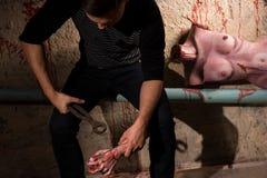 Αρσενική συνεδρίαση στο σωλήνα με έναν αιματηρό κορμό μιας νεκρής γυναίκας επάνω στοκ φωτογραφία
