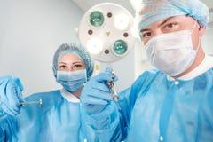 Αρσενική σύριγγα εκμετάλλευσης χειρούργων που απομονώνεται σε ένα άσπρο υπόβαθρο Εστίαση στη σύριγγα Στοκ εικόνες με δικαίωμα ελεύθερης χρήσης