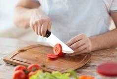 Αρσενική τέμνουσα ντομάτα χεριών εν πλω με το μαχαίρι Στοκ Φωτογραφία