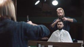 Αρσενική τέμνουσα τρίχα κουρέων του ατόμου σε Barbershop φιλμ μικρού μήκους