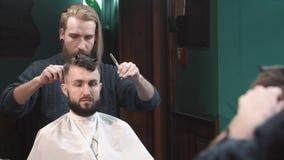 Αρσενική τέμνουσα τρίχα κουρέων του ατόμου σε Barbershop απόθεμα βίντεο