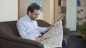 Αρσενική ταξιδιωτική συνεδρίαση στον καναπέ και εξέταση το χάρτη, που επιλέγει τη διαδρομή για τις διακοπές απόθεμα βίντεο