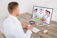 Αρσενική τηλεοπτική σύσκεψη γιατρών στον υπολογιστή Στοκ φωτογραφία με δικαίωμα ελεύθερης χρήσης