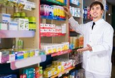 Αρσενική τοποθέτηση φαρμακοποιών στο φαρμακείο στοκ φωτογραφίες