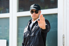Αρσενική φρουρά ασφάλειας που κάνει τη στάση να υπογράψει με το χέρι Στοκ Φωτογραφία