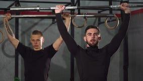 Αρσενικοί αθλητές crossfit που θερμαίνουν στη γυμναστική που ανυψώνει barbells φιλμ μικρού μήκους