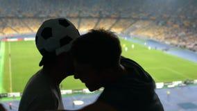 Αρσενικοί ανεμιστήρες εξαιρετικά ευχαριστημένοι από τη νίκη αγώνων ποδοσφαίρου, υψηλός-πέντε και τα αγκαλιάσματα, χαρά φιλμ μικρού μήκους