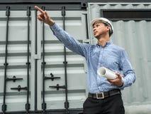 Αρσενικοί αρχιτέκτονας και σχεδιαγράμματα μηχανικών με το άσπρο κράνος που δείχνει το δάχτυλο σε ένα εργοτάξιο οικοδομής, αρχιτέκ στοκ φωτογραφίες